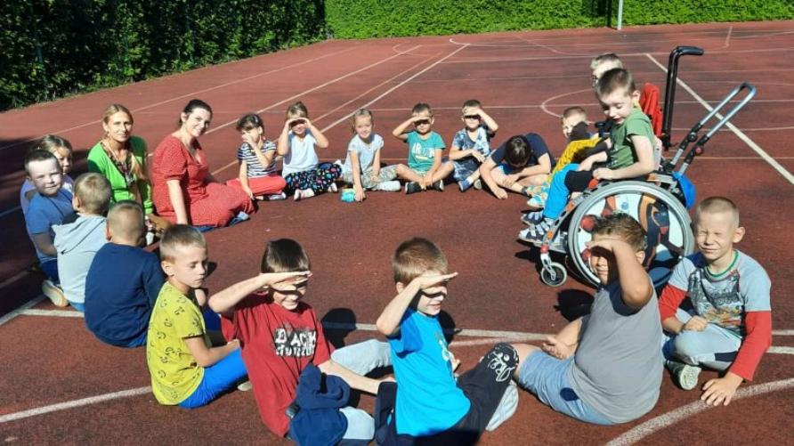 Dzieci siedzące w kręgu podczas zajęć z pedagogiem